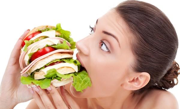 太りたいと食べ物をほおばる女性